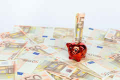 Small red piggy bank on many euro notes Stock Photo