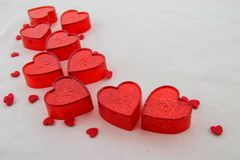 Small red plastic hearts with bright dots and tiny red hearts. Valentines day concept. Small red plastic hearts with bright dots and tiny red hearts on a white stock images