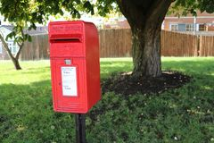Small red post box on residential street in UK Royalty Free Stock Image