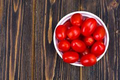 Small red ripe tomatoes in bowl on wooden table, top view. Studio Photo Stock Images