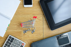 Small red shopping cart, trolley and gadgets on the table. Shopping online concept Royalty Free Stock Images