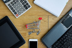 Small red shopping cart, trolley and gadgets on the table Stock Photos
