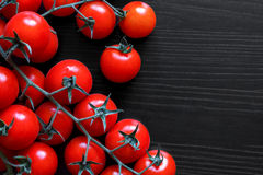 Small red tomatoes on the vine on black wood from above. Stock Images