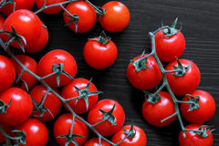 Small red tomatoes on the vine on black wood from above. Stock Photography
