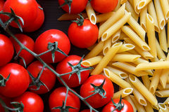 Small red tomatoes on the vine, dry penne pasta, on black wood f Royalty Free Stock Photo