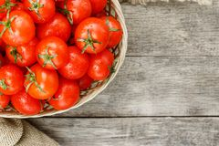 Small red tomatoes in a wicker basket on an old wooden table. Ripe and juicy cherry. And burlap cloth, Terevan style country style View from above stock photography