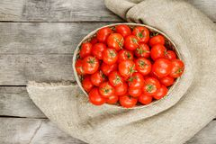 Small red tomatoes in a wicker basket on an old wooden table. Ripe and juicy cherry. And burlap cloth, Terevan style country style View from above royalty free stock images