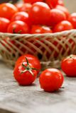 Small red tomatoes in a wicker basket on an old wooden table. Ripe and juicy cherry. And burlap cloth, Terevan style country style Vertical frame stock images