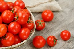 Small red tomatoes in a wicker basket on an old wooden table. Ripe and juicy cherry. And burlap cloth, Terevan style country style. selective royalty free stock photo
