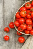 Small red tomatoes in a wicker basket on an old wooden table. Ripe and juicy cherry. And burlap cloth, Terevan style country style Vertical frame royalty free stock image