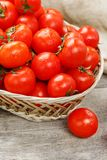 Small red tomatoes in a wicker basket on an old wooden table. Ripe and juicy cherry. And burlap cloth, Terevan style country style Vertical frame royalty free stock images
