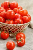 Small red tomatoes in a wicker basket on an old wooden table. Ripe and juicy cherry. And burlap cloth, Terevan style country style Vertical frame stock photography