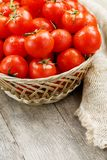 Small red tomatoes in a wicker basket on an old wooden table. Ripe and juicy cherry. And burlap cloth, Terevan style country style Vertical frame stock photo