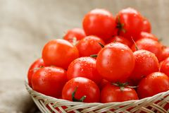 Small red tomatoes in a wicker basket on an old wooden table. Ripe and juicy cherry. And burlap cloth, Terevan style country style. selective focus stock image