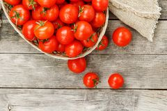 Small red tomatoes in a wicker basket on an old wooden table. Ripe and juicy cherry. And burlap cloth, Terevan style country style View from above stock photo