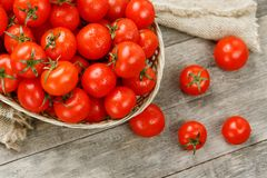 Small red tomatoes in a wicker basket on an old wooden table. Ripe and juicy cherry. And burlap cloth, Terevan style country style View from above royalty free stock photo