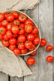Small red tomatoes in a wicker basket on an old wooden table. Ripe and juicy cherry. And burlap cloth, Terevan style country style Vertical frame royalty free stock photography