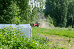 Small red tractor harrow ground  near homestead Royalty Free Stock Photos