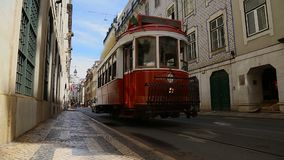 Small red tram arriving at stop in order to pick up people, urban transportation