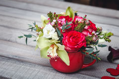 Small red vase with bouquet of flowers and Lilies on wooden table space for text Royalty Free Stock Photo