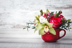 Small red vase with bouquet of flowers and Lilies on wooden table space for text Stock Photography
