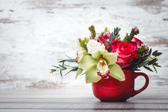 Small red vase with bouquet of flowers and Lilies on wooden table space for text Royalty Free Stock Photography