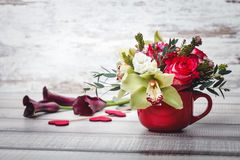 Small red vase with bouquet of flowers and Lilies on wooden table space for text Stock Photos