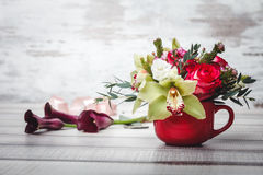 Small red vase with bouquet of flowers and Lilies on wooden table space for text Royalty Free Stock Photos