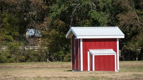 Small red and white shed in grassy field stock photos