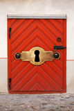 Small Red wooden door with large keyhole Stock Images