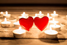 Small red wooden hearts and candles Stock Image