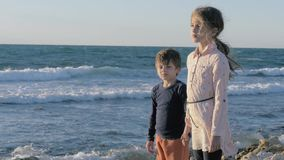 Small refugees brother and sister were left alone on the beach and waiting for help. stock footage