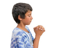 Small religious gypsy kid boy praying with folded hands side vie Stock Photo
