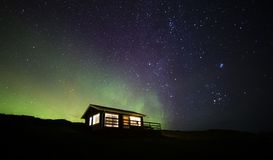 Northern lights cabin. A small remote cabin in Iceland, under a night sky displaying the northern lights stock image