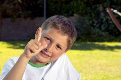 Small request. A child who pointed out in the sun in the park Stock Photo