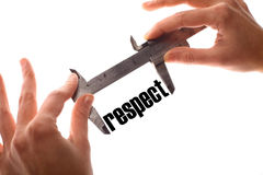 Small respect. Color horizontal shot of two hands holding a caliper and measuring the word respect Royalty Free Stock Image