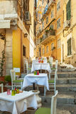 Small restaurant standing on typical narrow street Stock Photos