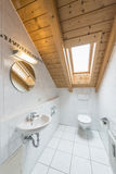 Small restroom. Picture of a white tiled restroom with tiolet, basin, mirror and light Stock Image