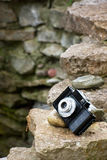 Small retro SLR film camera on rocks Stock Images