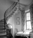 Small retro window room. A round table at a window, small room with the winding stairs going up. Retro feeling. Monochrome image Royalty Free Stock Photos