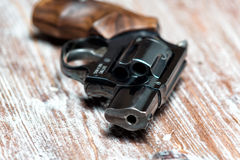 Small revolver lying on a  table. Small revolver lying on a wooden table, shallow depth of field Royalty Free Stock Images
