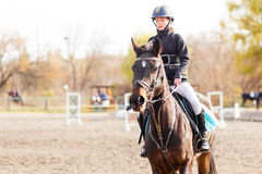 Small rider girl on show jumping competition. Small rider girl on horseback on show jumping competition Royalty Free Stock Images