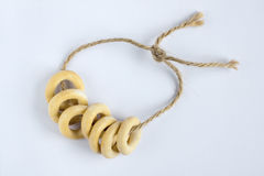 Small ring-shaped crackers on rope. Small ring-shaped crackers called sooshka or bagel are on rope is traditional snack for tea in Russia Royalty Free Stock Photos