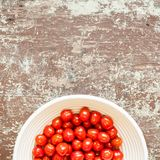 Small ripe organic cherry tomatoes in a bowl on old wood table royalty free stock image