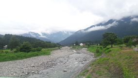 The small river with the background of the mountain covered with cloud royalty free stock images
