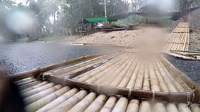 Small river bank on a rainy day. Bank of a small river with several huts and bamboo rafts on a rainy day on Phuket island stock footage