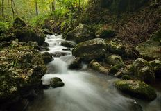 Small river cascade. View on the small river cascade over stones in forest Royalty Free Stock Photos