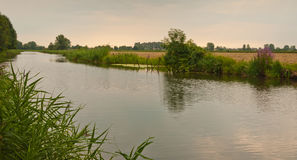 Small river with colorful banks and fields. In the Netherlands Stock Image