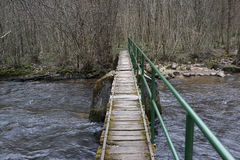 Small river crossing. A small bridge crosses a river in a forest Stock Image