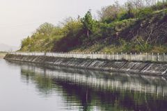 Small River Dam Concrete Wall. With Fence And Green Plants At The Back Stock Photo